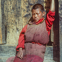 A young Tibetan Buddhist monk sits in a doorway in Namche Bazar in the Khumbu region of Nepal's Himalaya.