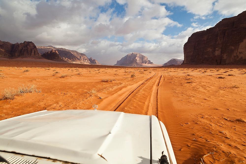 A jeep drives through the desert towards high sandstone cliffs in Wadi Rum, Jordan.
