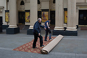 Carpet fitters unroll a new carpet in the street for the interior of the Lyceum Theatre on Wellington Street, on 5th March 2019, in London, England.