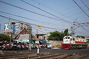 Mopeds and motorbikes at a busy level crossing over the railway on 9th June 2018, Jakarta, Java, Indonesia. There are thousands of mopeds on the streets of Jakarta.