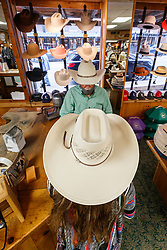 Hat fitter fitting cowboy hat for lady,  M.L Leddy's Boots, Fort Worth Stockyards National Historic District, Fort Worth, Texas, USA.