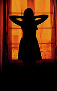 Silhouette of a woman indoors, wearing a dress