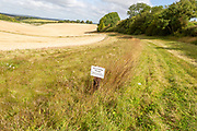 Sign for stewardship margin conservation strip of land in arable field, Inkpen Hill, Berkshire, England, UK