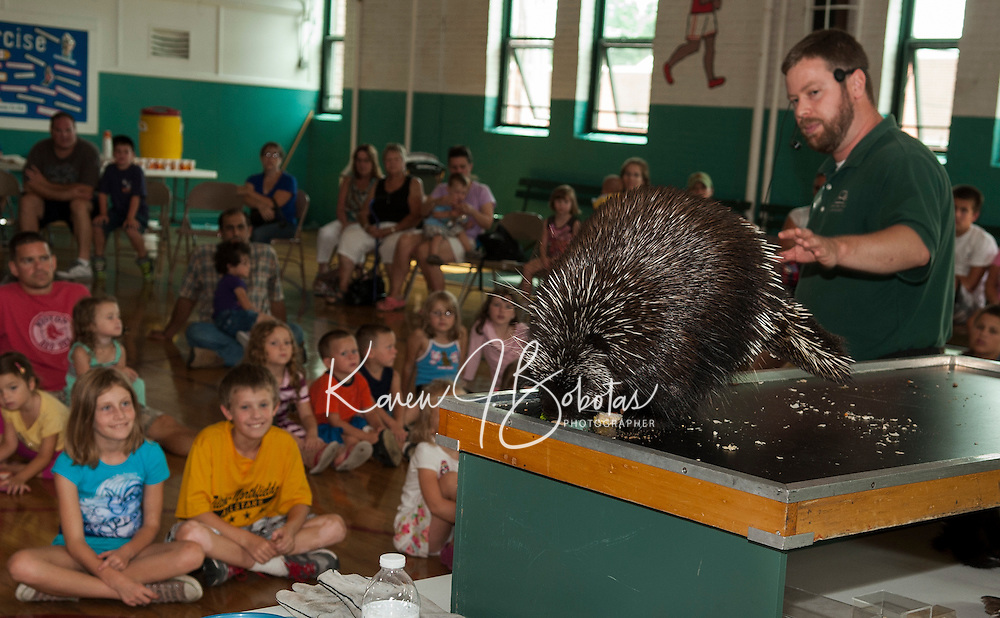 Squam Lakes Science Center's Jeremy Phillips explains the porcupines quills to the children gathered for Laconia's Summer Reading program event at the Community Center Wednesday afternoon.  (Karen Bobotas/for the Laconia Daily Sun)