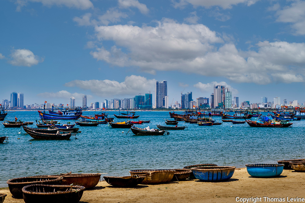 Da Nang cityscape from across the bay with fishing boats by the shore.