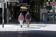 A pair of walkers on Swanston St cross an empty Bourke Street Mall on the first day of a five day snap lockdown in Victoria due to COVID-19 outbreak originating at The Holiday Inn. The entire state is returning to harsh stage-four lockdowns until Wednesday at 11.59pm as health authorities struggle to contain the Holiday Inn coronavirus outbreak.
