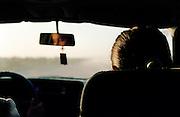 A woman in a car driving through barren China