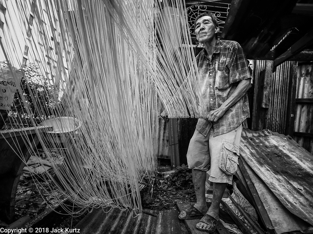 """29 DECEMBER 2018 - BANGKOK, THAILAND: A man stretches longevity noodles in front of his family shophouse. The family has been making traditional """"mee sua"""" noodles, also called """"longevity noodles"""" for three generations in their home in central Bangkok. They use a recipe brought to Thailand from China. Longevity noodles are thought to contribute to a long and healthy life and  are served on special occasions, especially Chinese New Year, which is February 4, 2019. These noodles were being made for Chinese New Year.    PHOTO BY JACK KURTZ"""