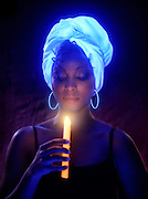 Woman with glowing turban, ear rings and candles.Black light