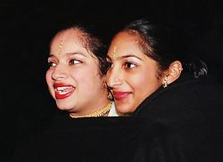 Two teenage girls standing together in crowd celebrating Diwali; festival of light; sheltering for warmth under blanket,