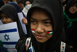 June 23, 2017 - Central Jakarta, Jakarta, Indonesia - Indonesian Muslim with Indonesia and Palestine flag sticker on they face during a pro-Palestinian rally marking the International Al-Quds (Jerusalem) Day outside the U.S. Embassy in Jakarta, Indonesia on June 23, 2017. Al Quds Day (Jerusalem Day) is an annual event held on the last Friday of Ramadan that was initiated by the Islamic Republic of Iran in 1979 to express support for the Palestinians and oppose Zionism and Israel, as well as Israel's occupation of Jerusalem and Jewish settlements in Israeli-occupied territories. (Credit Image: © Afriadi Hikmal via ZUMA Wire)