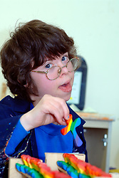 Young woman with Downs Syndrome painting wooden rainbow crosses at a workshop for people with learning difficulties UK
