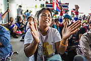 """08 APRIL 2014 - BANGKOK, THAILAND: An anti-government protestor applauds for Suthep Thaugsuban at the Ministry of Justice in Bangkok. Several hundred anti-government protestors led by Suthep Thaugsuban went to the Ministry of Justice in Bangkok Tuesday. Suthep and the protestors met with representatives of the Ministry of Justice and expressed their belief that Thai politics need to be reformed and that corruption needed to be """"seriously tackled."""" The protestors returned to their main protest site in Lumpini Park in central Bangkok after the meeting.    PHOTO BY JACK KURTZ"""