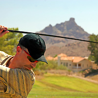 USA, Arizona, Fountain Hills. Male golfer ready to swing with the Red Mountain in the background.