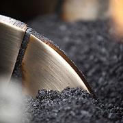 Closeup, interior view of hot asphalt inside of paving machine.