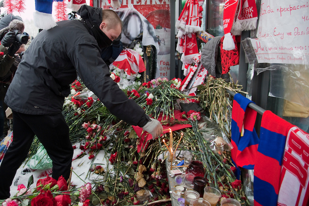 Moscow, Russia, 15/01/2011..A masked football fan lights candles during a rally at the bus stop where Spartak soccer fan Yegor Sviridov was killed in a street fight with a group of men from the southern Caucasus, leading to a nationalist backlash that has spilled into racist violence on the streets of Moscow and other Russian cities. The rally on the 40th day after Sviridov's death was attended by a mixture of local people, football fans and Russian nationalists.