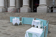 Vacant tables await customers within social distance street barriers where Fortnum & Masons have set up an outdoor restaurant and bar in front of the Royal Exchange at Bank, in the City of London, during the second wave of the Coronavirus pandemic, and when the capital is designated by the government as a Tier 2 restriction, on 20th October 2020, in London, England.
