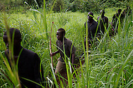 """A boy patrols his community with the local """"arrow boy"""" force, to defend against the LRA."""
