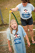 A competitor is hosed off after rolling around in a pool of instant grits during the grits roll competition at the World Grits Festival April 14, 2012 in St. George, SC. The festival celebrates the southern love for the sticky corn porridge