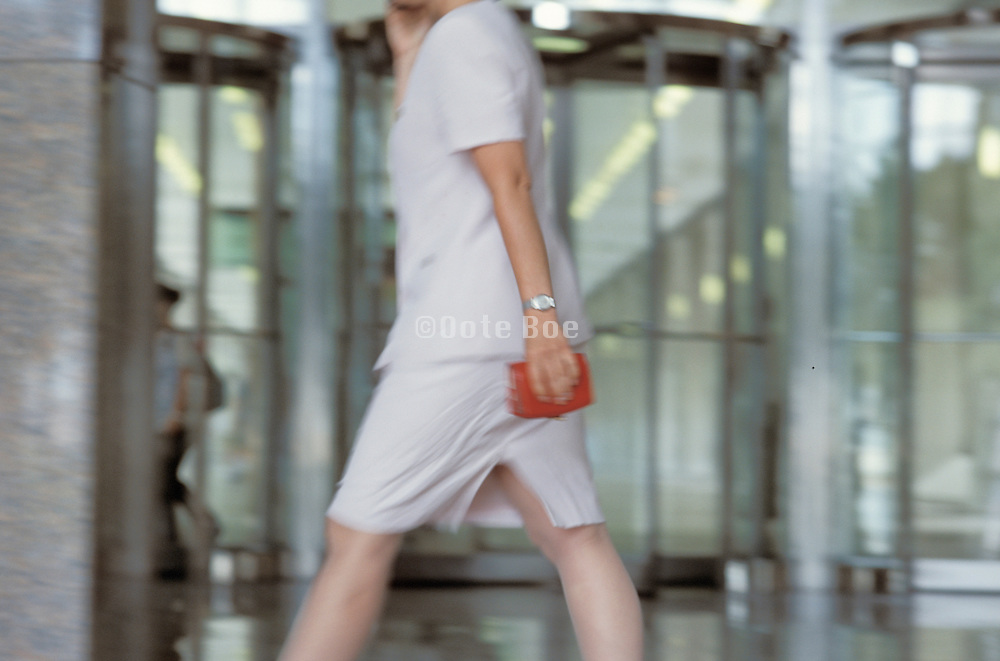 business woman waking in the lobby of an office