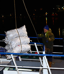 Skipper Ian Fletcher of the Rois Mairi landing bags of clams at the pier John MacaAister Oban ltd  in a rush to get them despatched so they have more of a chance to make their destination in france picture kevin mcglynn