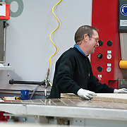 Smiling mature man working in factory
