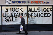 An all reduced sale of sports clothing supplier JJB.com stock, being sold by new buyer, Sports Direct shop in central London. A male shopper walks past the store window with a Sports Direct bag, passing the large lettering painted onto the glass, declaring the stock sale. <br />