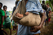 A mother carries her child in Yar village in Papua New Guinea's East Sepik Province. (June 23, 2019)