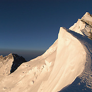 Gazing up the sweeping cornices and rock steps of Everest's Northeast Ridge from Mushroom Rock at 28,300 feet. Lhotse rises behind and left.