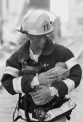 Working fireman carrying a baby
