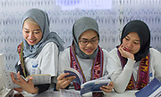Three young women reading during day one of the London Book Fair at Kensington Olympia on the 12th March 2019 in London in the United Kingdom.