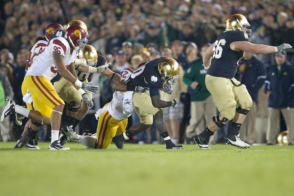 USC defensive end Devon Kennard (#42) makes tackle on Notre Dame running back Cierre Wood (#20) during third quarter of NCAA football game between Notre Dame and USC.  The USC Trojans defeated the Notre Dame Fighting Irish 31-17 in game at Notre Dame Stadium in South Bend, Indiana.