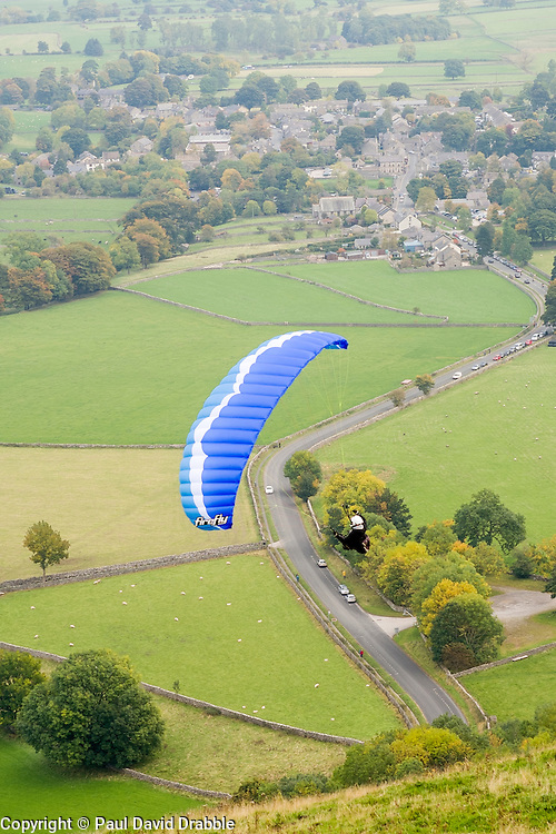 A paraglider flies from the hills around Mam Tor with Castleton in the background <br />  11 October 2015<br />   Image © Paul David Drabble <br />   www.pauldaviddrabble.co.uk