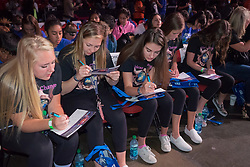 Teen girls completing commitment form at We Day 2015, Seattle, Washington. Free the Chldren event which inspires youth activism and volunteering.