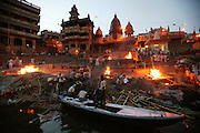 Bodies arrive day and night from far and near to be cremated at Jalasi Ghat, the cremation grounds at Manikarnika Ghat, Varanasi, India. One hundred or more times a day male family members carry a loved one's body through the narrow streets on a bamboo litter to the Ganges River shore, a place of pilgrimage for Hindus during life, and at death.