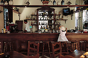 A young girl in dress up clothes and sun hat has a cold drink at a hotel bar in old Havana, Cuba.