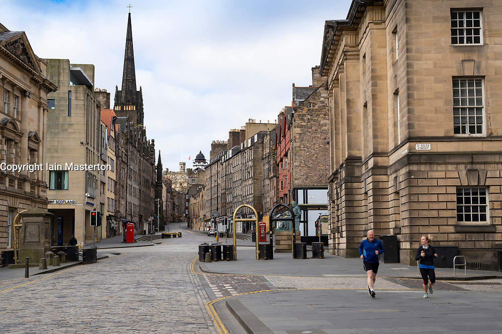 Edinburgh, Scotland, UK. 18 April 2020. Views of empty streets and members of the public outside on another Saturday during the coronavirus lockdown in Edinburgh. The Royal Mile is empty apart from two runners. Iain Masterton/Alamy Live News