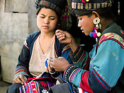 Two Mouchi ethnic minority women (sisters) sew traditional clothing outside their home in Ban Nam Sa, Phongsaly province, Lao PDR.  One of the most ethnically diverse countries in Southeast Asia, Laos has 49 officially recognised ethnic groups although there are many more self-identified and sub groups.  These groups are distinguished by their own customs, beliefs and rituals. Details down to the embroidery on a shirt, the colour of the trim and the type of skirt all help signify the wearer's ethnic and clan affiliations.