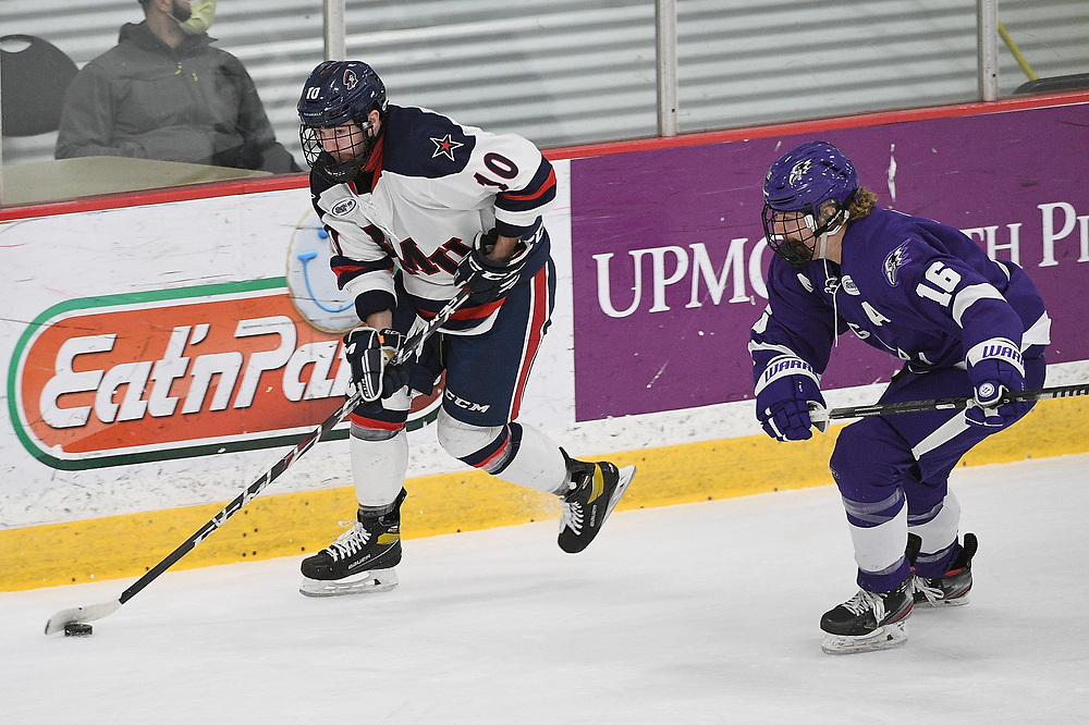PITTSBURGH, PA - MARCH 13: Nick Lalonde #10 of the Robert Morris Colonials skates with the puck under pressure from Jared Brandt #16 of the Niagara Purple Eagles in the first period during Game Two of the Atlantic Hockey Quarterfinal series at Clearview Arena on March 13, 2021 in Pittsburgh, Pennsylvania. (Photo by Justin Berl/Robert Morris Athletics)