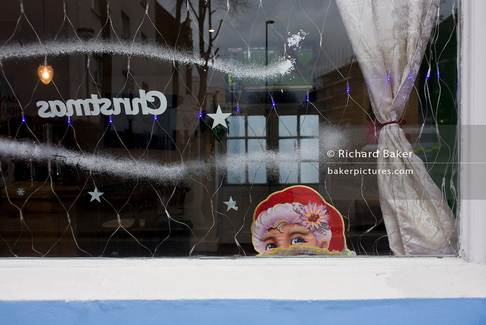 The face of Santa peers out through the window of a south London pub in the weeks before Christmas.