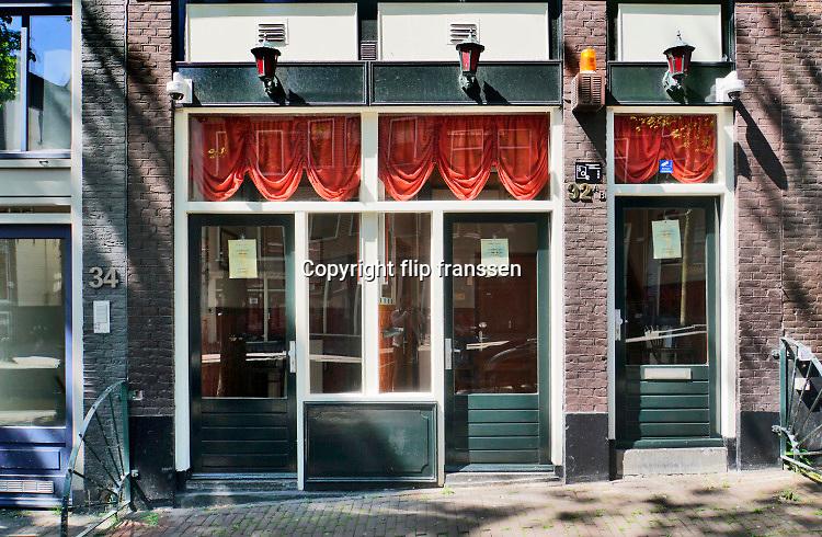 Nederland, Amsterdam, 7-5-2020 Gesloten kamers van prostituees op de wallen .De regering laat het normale dagelijks leven weer langzaam opstarten . Door de afwezigheid van toeristen is het ongewoon rustig op de wallen en de rest van de binnenstad van Amsterdam en is de stad te zien zoals die pakweg voor de eeuwwisseling was . Op de bruggetjes over de grachten staan fietsen . ,geschiedenis, typisch,amsterdams,iconisch,historische,bebouwing,architectuur . Unlock,beperkende,beperkingen, opheffen,versoepelen,versoepeling , opengooien, massatoerisme,toeristisch, toeristische, hoeren,prostitutie,rood,kamers,sekswerker,sekswerkers .Foto: Flip Franssen