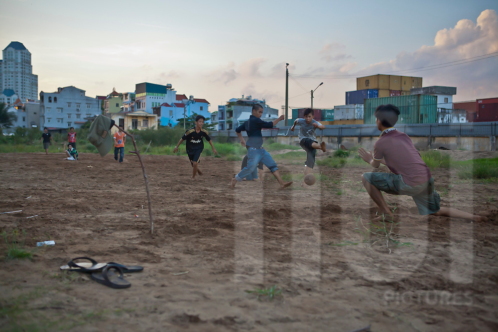 Vietnamese kids playing football on a waste land near a container park in Ho Chi Minh city (HCMC), Vietnam, Asia
