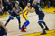 The Minnesota Timberwolves defend Golden State Warriors guard Stephen Curry (30) by grabbing his jersey at Oracle Arena in Oakland, Calif., on January 25, 2018. (Stan Olszewski/Special to S.F. Examiner)