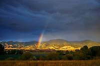 A rainbow appears in front of the Bridger Mountains in Bozeman, Montana during a fall rain storm.