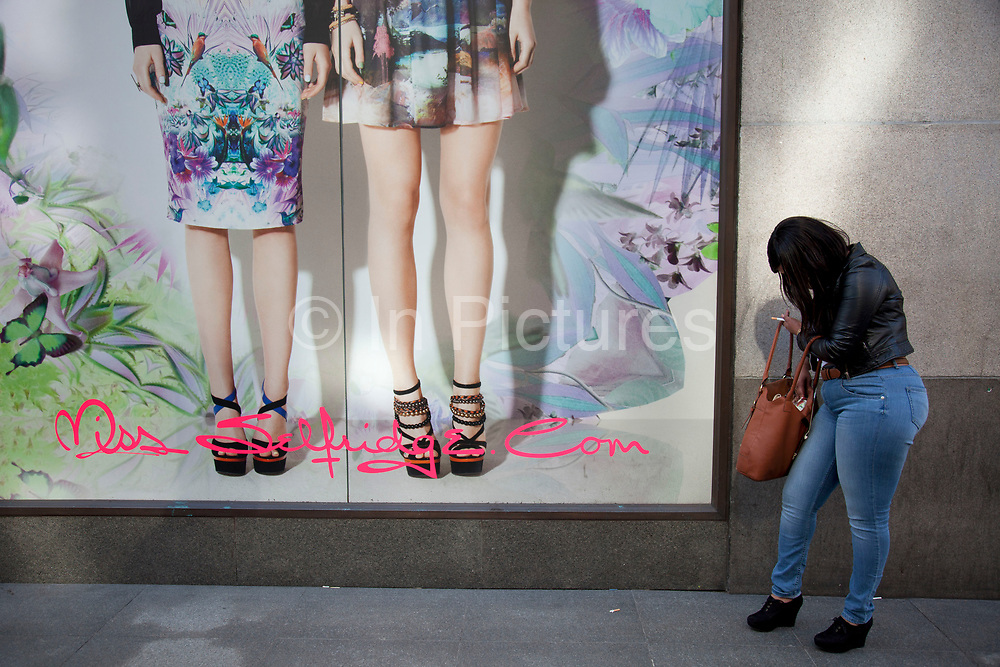 Woman outside Miss Selfridge retail store in contrast in scale in front of the large photographic advertising hoardings dipicting slender models. Shoppers in central London on Oxford Street. UK.