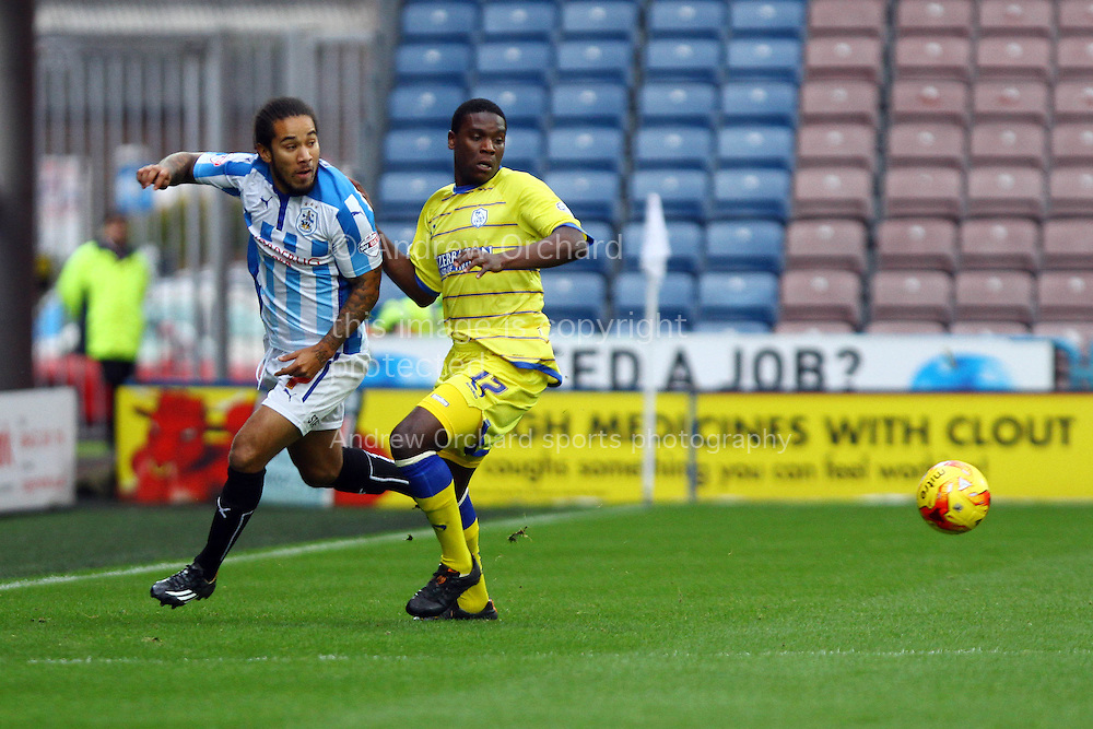 Sean Scannell of Huddersfield Town and Gary Taylor-Fletcher of Sheffield Wednesday chase the ball. Skybet football league championship match, Huddersfield Town v Sheffield Wednesday at the John Smith's stadium in Huddersfield, Yorkshire on Saturday 22nd November 2014.<br /> pic by Chris Stading, Andrew Orchard sports photography.
