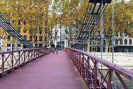 Lyon, France--November 5, 2017--Two cyclists are riding thier bicycles over the Saint Vincent Bridge in Lyon. Editorial Use Only.