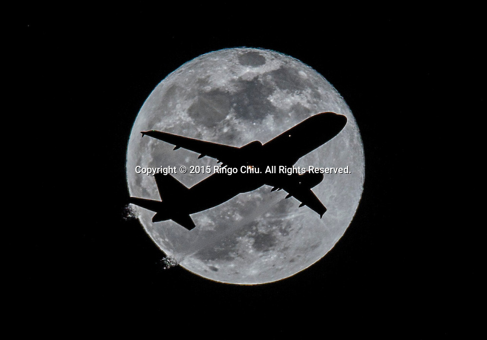 An airplane approaching Los Angeles International Airport flies past the full moon in Los Angeles, California, on April 4, 2015.