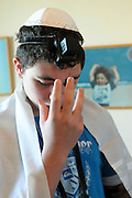 Bar Mitzvah ceremony A young boy of 13 laying Tefillin