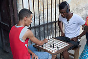 Young Cuban men playing chess in the street, Havana.